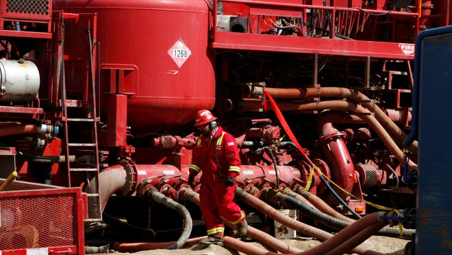 An unidentified worker steps through the maze of hoses being used at a remote fracking site being run by Halliburton. Halliburton profits slipped due to a glut of natural gas.