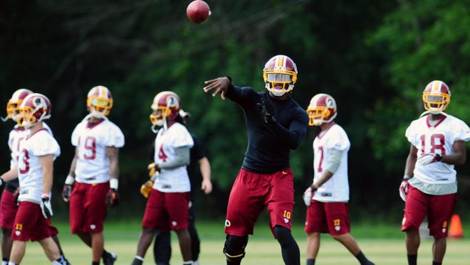 Redskins QB Robert Griffin III spent most of OTAs throwing to injured teammates on side fields at Redskins Park.