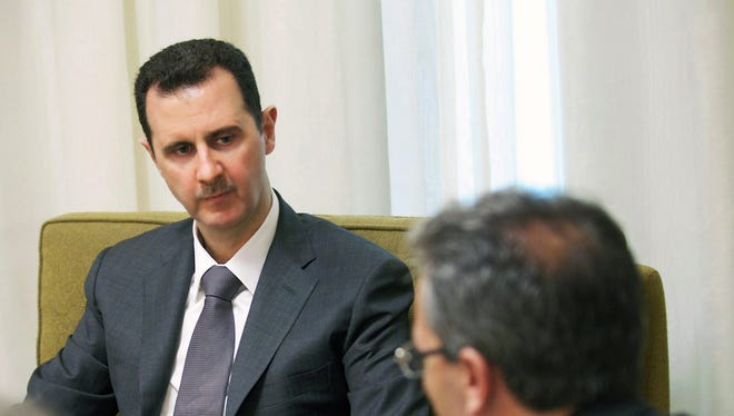 Syrian President Bashar Assad, center, speaks during an interview published with the state-run Al-Thawra newspaper, in Damascus, Syria.