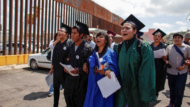"""""""DREAMers"""" wearing their school graduation caps and gowns to show their desire to finish school in the U.S., march with linked arms to the U.S. port of entry where they planned to request humanitarian parole, in Nogales, Mexico, Monday, July 22, 2013."""