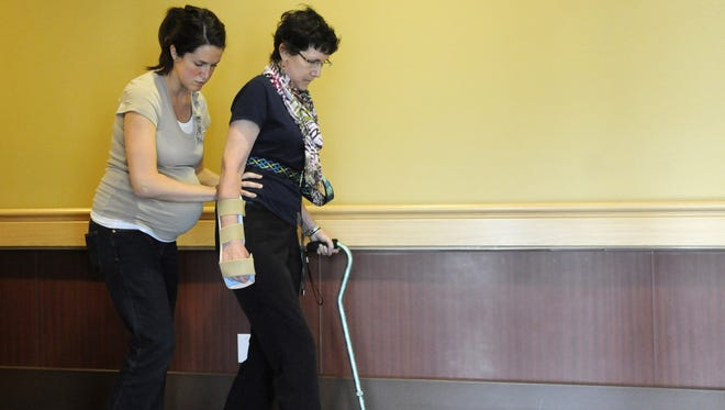 Jenny Deutz, left, helps Judy Miles walk during physical therapy at Quality Living Inc. in Omaha, Neb. on Tuesday, April 3, 2012. More Americans ages 40 through 50 are afraid of critical illness than they are of death.