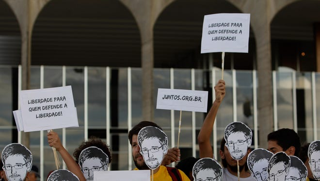 """Demonstrators hold cutouts depicting Edward Snowden and posters that read in Portuguese; """"Freedom for those who defend freedom,"""" at a protest in Brasilia, Brazil, on July 18."""