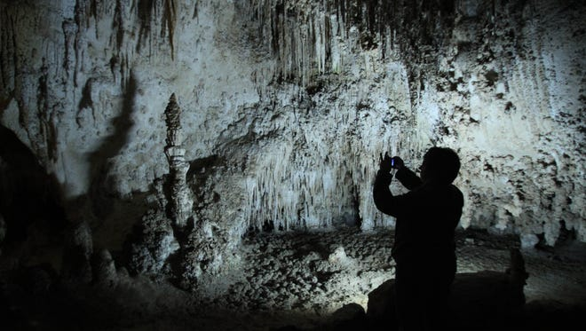 A visitor takes a photo of a cave formation inside Kings Palace at Carlsbad Caverns National Park near Carlsbad, N.M.