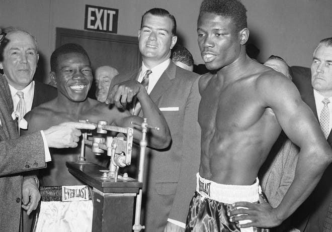 Welterweight champion Benny Paret, in white trunks, smiles as he reads the weight of challenger and former champion Emile Griffith during the weigh-in for their title fight in New York in March 1962. Paret taunted Griffith during the weigh-in, calling him the Spanish word for homosexual.