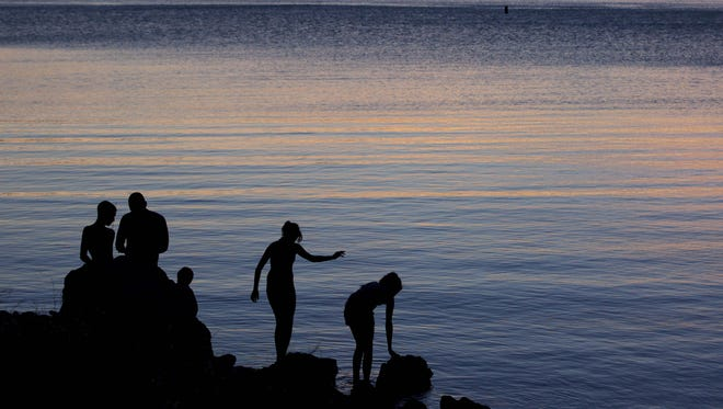 Jeffery Serrano, of Henderson, Nev., second from left, helps his kids fish at twilight at the edge of Kingman Wash, at Lake Mead National Recreation Area in Arizona, May 27, 2011.