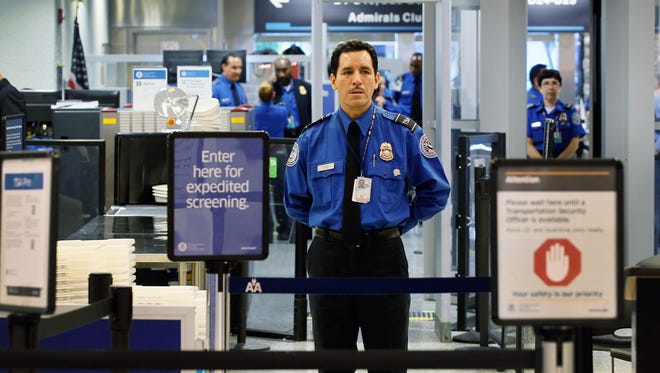 A TSA agent stands on duty at the PreCheck lane at Miami International Airport.