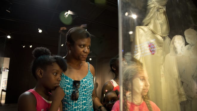 Rozenia Moore, middle, talks to her grandchildren Taylor Grace, 9, left,  Kennedy Grace, 5, Kyla Grace, 11 and family friend Bella Borhani, 10, in pigtails, right, from New York, about the KKK uniform on display at the the Birmingham Civil Rights Institute.