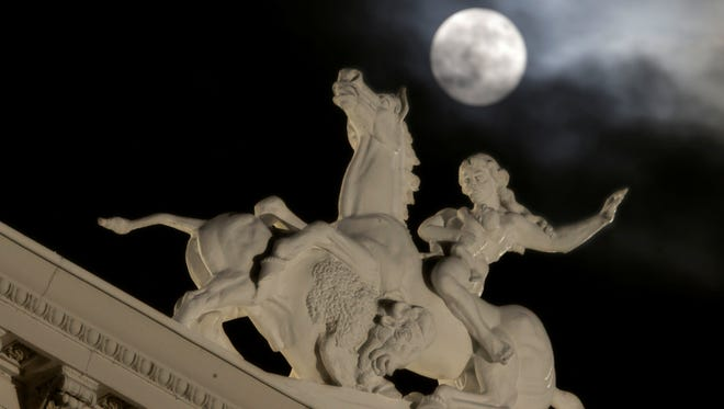 A statue atop the California Capitol is seen as the full moon peeks through the clouds over Sacramento, Calif., June 23 2013.