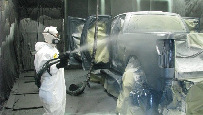 Technician Roland Mendoza sprays bedliner material on the sides of a Toyota Tundra pickup truck in a booth at the Line-X Orange County shop in Anaheim, Calif.