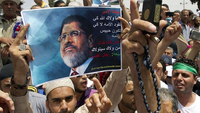 A demonstrator holds a portrait of deposed Egyptian President Mohamed Morsi during a rally by supporters of the radical Islamist movement Hamas on July 19 outside al-Aqsa Mosque compound in Jerusalem.