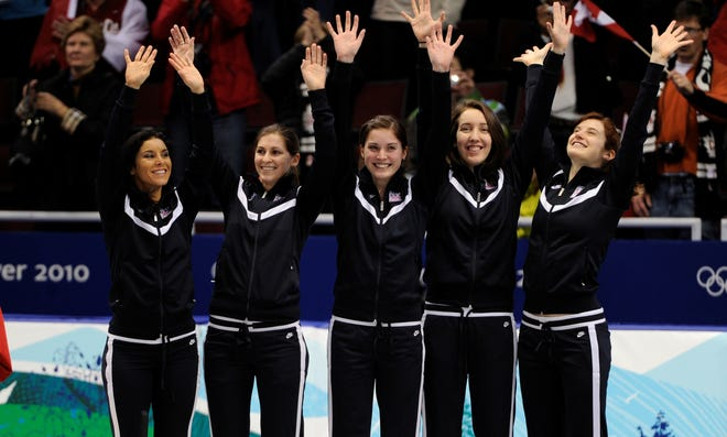 In a file photo from the 2010 Vancouver Games, the U.S. women's 3000-meter relay team of Allison Baver, left, Kimberly Derrick, Alyson Dudek, Lana Gehring and Katherine Reutter wave after winning the bronze medal.