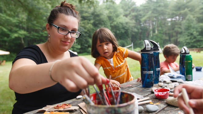 Victoria Esselman, 16, paints rocks with Isabella Scherl, 4, during a camp session July 10 in Exeter, R.I. Esselman who was diagnosed with pediatric MS when she was 12, attends Teen Adventure Camp, created and run by the Lourie Center for Pediatric MS at Stony Brook University Medical Center.