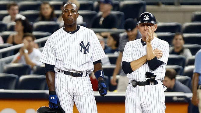 New York Yankees left fielder Alfonso Soriano stands at first with first base coach Mick Kelleher during the ninth inning at Yankee Stadium.