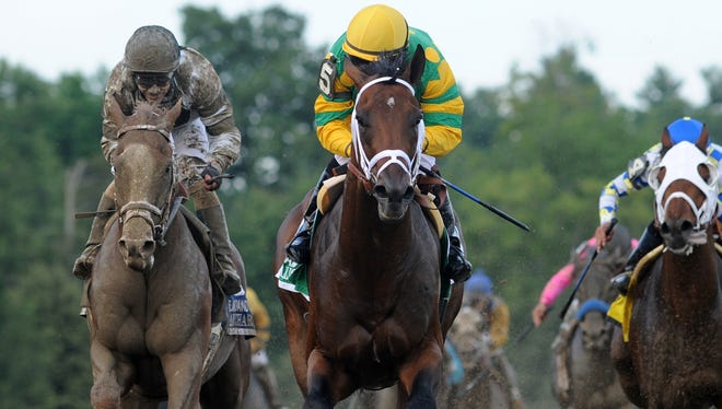 Palace Malice, center, with jockey Mike Smith, yellow silks, captures the Jim Dandy Stakes at Saratoga Race Course on Saturday.