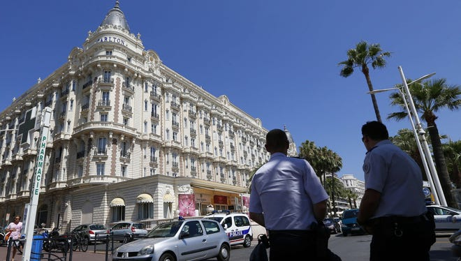 French policemen keep watch outside the Carlton Hotel on July 28 in the French Riviera resort of Cannes, after an armed man stole an estimated $53 million worth of jewels, according to investigators.