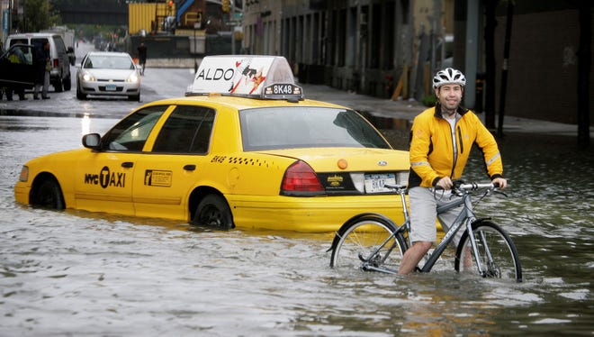 A bicyclist makes his way past a stranded taxi on a flooded New York City street Aug. 28, 2011, as Tropical Storm Irene passes through the city.