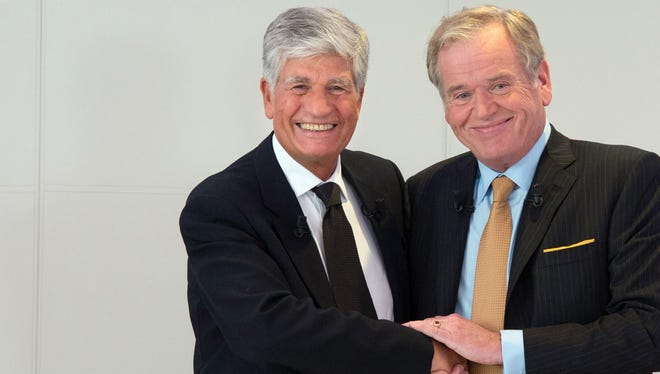 Publicis Group CEO Maurice Levy, left, shakes hands with Omnicom Group CEO John Wren during a press conference on Sunday in Paris.