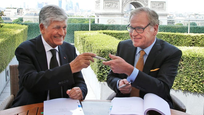 Maurice Levy, left, CEO of Publicis, and John Wren, head of Omnicom Group exchange a pencil during a joint signature prior to a news conference in Paris, France, on Sunday.