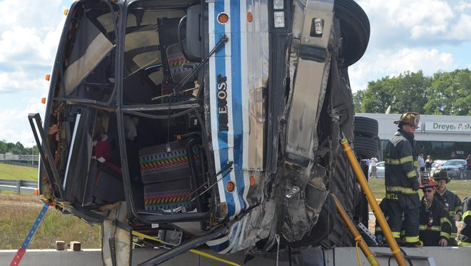 A charter bus carrying 37 passengers and the driver is stabilized after it overturned on Saturday, July 27, 2013.