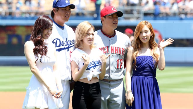 South Korean players Hyun-Jin Ryu of the Dodgers and Shin-Soo Choo of the Reds pose with Korean Pop group Girls Generation (L to R) tiffany, Sunny, and Taeyeon during Korea Day ceremonies before the game at Dodger Stadium.