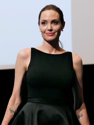 Angelina Jolie poses for photographers before screening the film 'In the Land of Blood and Honey' directed by her, at the United Nations University in Tokyo on Monday.