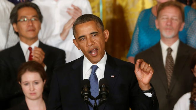 President Obama stands with families who have benefited from the 2010 health care law on July 18.