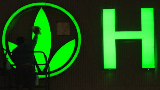 A worker cleans the logo on the Herbalife sign as finishing touches are put on the company's building in Torrance, Calif., in 2006. Herbalife's quarterly earnings increased 8% in the last quarter over last year.