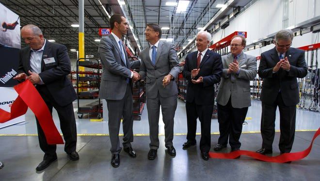 Gov. Pat McCrory, center, and Lenovo President for North America Jay Parker shake hands as the worldís second-largest PC vendor hosts a grand opening at its U.S. production facility on June 5 in Whitsett, N.C.
