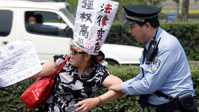 A Chinese police officer tries to restrain a Chinese petitioner protesting against corruption and legal injustice on a road near a hotel in Beijing in 2009.