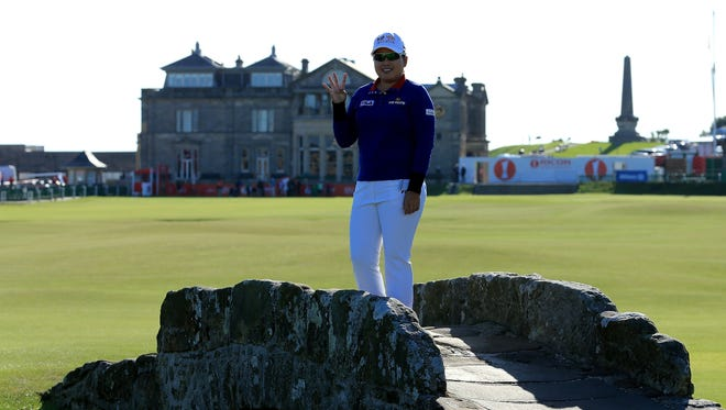 Inbee Park of South Korea holds up four fingers from the Swilken Bridge on the 18th hole at the Ricoh Women's British Open on the Old Course at St. Andrews, Scotland.