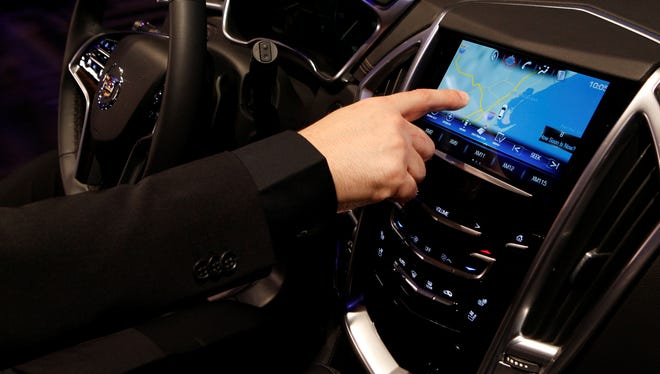 Mike Hichme,  engineering manager for the Cadillac Cue, demonstrates the touch screen aspect of the system, which does not have a slot for CDs.
