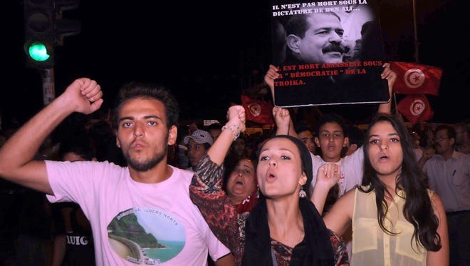 Tunisians chant slogans on July 30 in front of the Constituent Assembly headquarters during a protest against the country's Islamist government in Tunis.