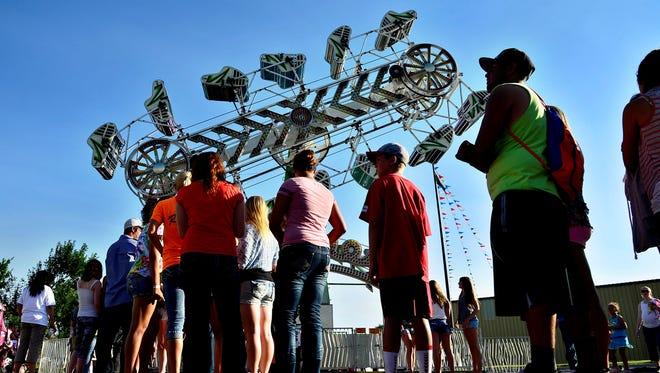 People stand in line for the Zipper ride at the Montana State Fair on Friday, July 26, 2013. A female rider fell from the Zipper on Tuesday, July 30, 2013.