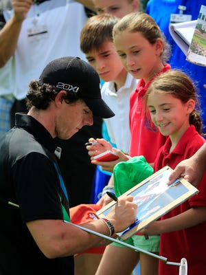 Rory McIlroy of orthern Ireland signs autographs during a practice round prior to the World Golf Championships-Bridgestone Invitational at Firestone Country Club.