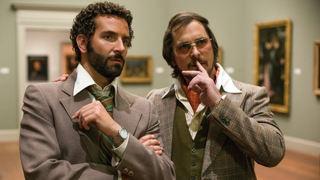 Richie Dimaso (Bradley Cooper, left) and Irving Rosenfeld (Christian Bale) talk in a gallery at the Frick Museum  in a scene from the movie 'American Hustle.'