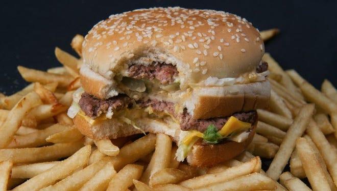 A photo of a partially eaten McDonalds' Big Mac hamburger atop French fries, November 2, 2010.