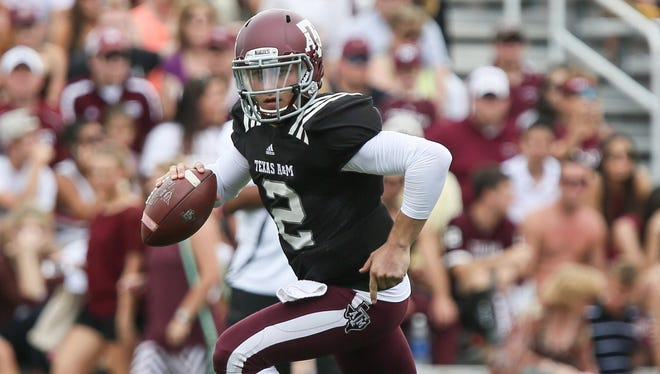 An ESPN report Sunday says Texas A&M quarterback and Heisman Trophy winner Johnny Manziel accepted cash for autographs, possibly ending his college eligibility.