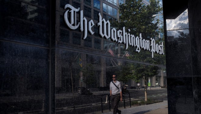 A man walks past The Washington Post on Monday after it was announced the iconic newspaper was being sold to Amazon founder Jeff Bezos.