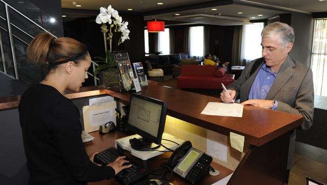Glenn Camus, of Pittsburgh, Pa., checks in at the front desk at Hotel Zero Degrees in Stamford, Ct.