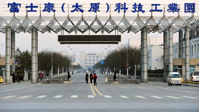 In this Nov. 22, 2011 photo, security guards stand at a gate of Foxconn's industrial zone in Taiyuan, the capital of Northern China's Shanxi province.