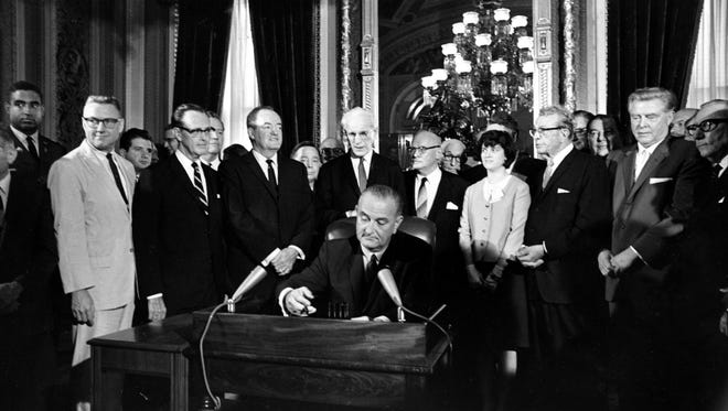 U.S. President Lyndon B. Johnson signs the Voting Rights Act of 1965 in a ceremony in the President's Room near the Senate chambers in Washington, D.C.