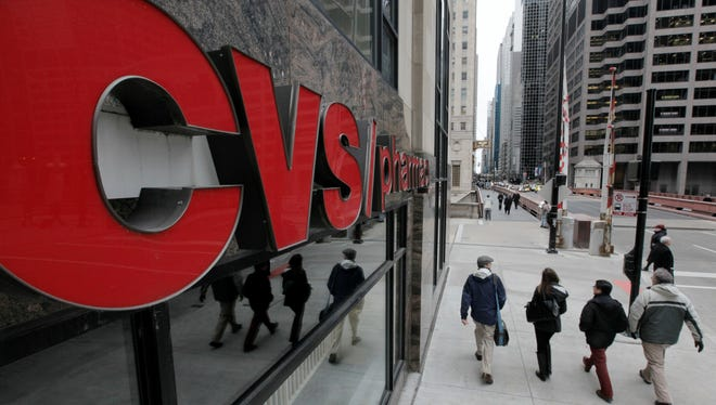 Pedestrians walk past a CVS store in Chicago in February 2012.