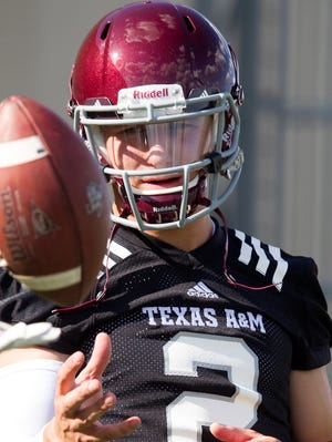 Texas A&M quarterback and Heisman Trophy winner Johnny Manziel warms up during football practice on Aug. 5.