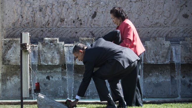 President Obama lays a rose at the grave of Cesar Chavez, with his widow Helen Chavez,  during a tour of a memorial garden at the Chavez National Monument.