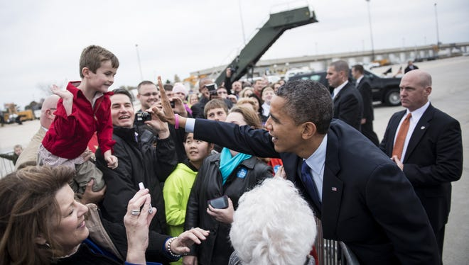 President Obama high-fives a boy while greeting supporters after arriving at Eastern Iowa Airport on Wednesday in Mount Vernon.