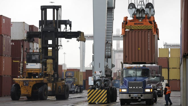 In this Dec. 18 photo, a truck driver watches as a freight container, right, is lowered onto a tractor trailer by a container crane at the Port of Boston.