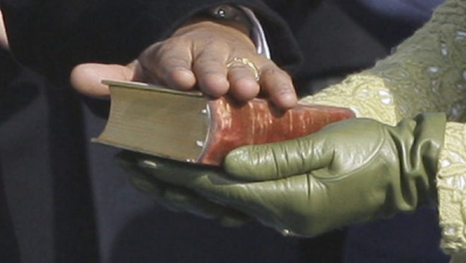President Obama rests his hand on President Lincoln's inaugural Bible as  his wife Michelle Obama holds it during the 2009 inauguration.