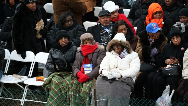 People try to stay warm before the presidential inauguration on the West Front of the U.S. Capitol.