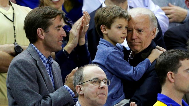 Vice President Biden holds his grandson, Hunter, next to his son, Beau, while watching Delaware and North Carolina in the women's NCAA college basketball tournament on March 26.