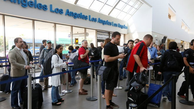 Travelers stand in line at Los Angeles International Airport.